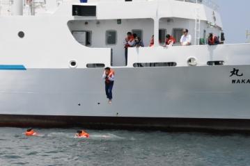デッキから海へ飛び込む学生